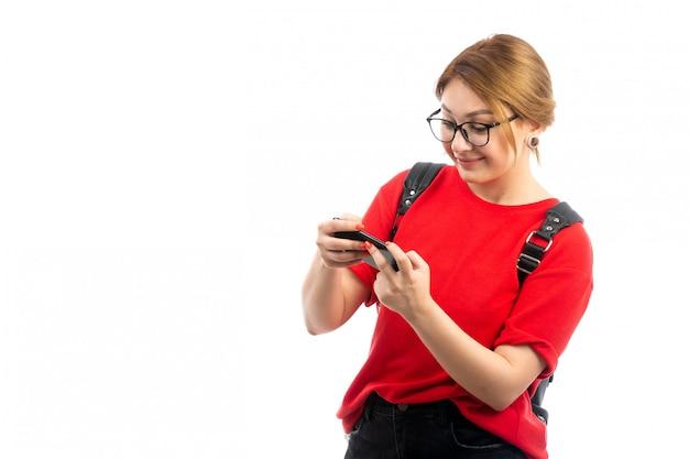Une vue de face jeune étudiante en t-shirt rouge portant un sac noir tenant un smartphone noir à l'aide de souriant sur le blanc