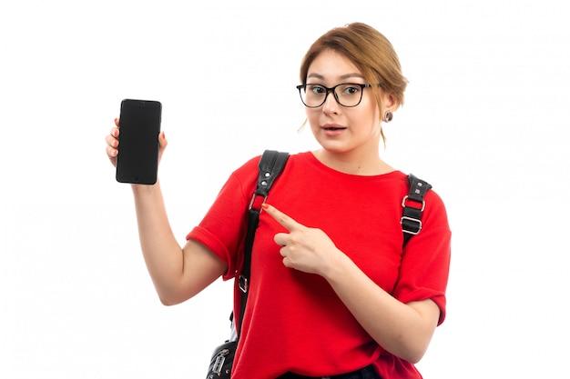 Une vue de face jeune étudiante en t-shirt rouge portant un sac noir tenant un smartphone noir sur le blanc
