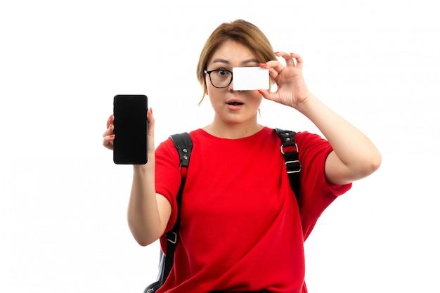 Une vue de face jeune étudiante en t-shirt rouge portant un sac noir tenant un smartphone noir et une carte blanche sur le blanc