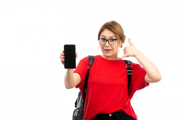 Une vue de face jeune étudiante en t-shirt rouge portant un sac noir tenant un smartphone noir souriant sur le blanc