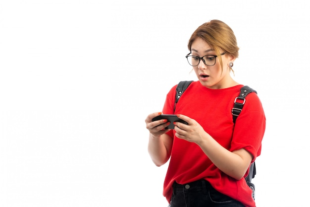 Une vue de face jeune étudiante en t-shirt rouge portant un sac noir tenant un smartphone noir en utilisant sur le blanc
