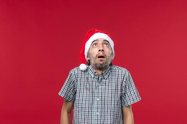 Vue de face jeune avec expression effrayée sur le mur rouge vacances nouvel an rouge