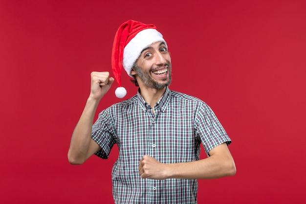 Vue de face jeune avec une expression excitée sur le mur rouge mâle de vacances nouvel an rouge