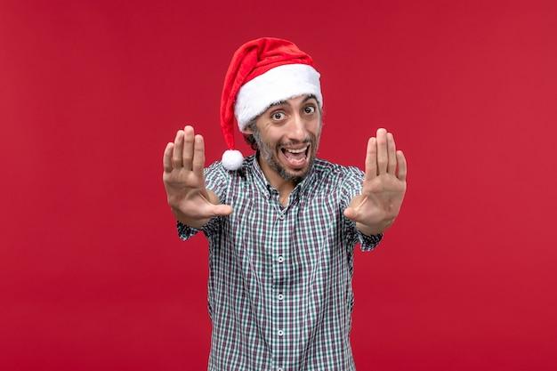Vue de face jeune avec une expression excitée sur le mur rouge vacances nouvel an mâle rouge