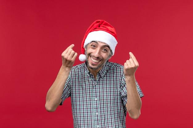 Vue de face jeune avec une expression heureuse sur le mur rouge vacances nouvel an rouge