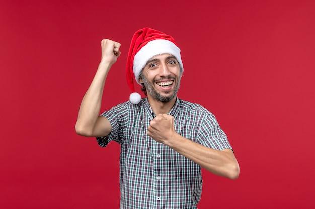 Vue de face jeune avec une expression souriante sur le mur rouge rouge nouvel an vacances mâle