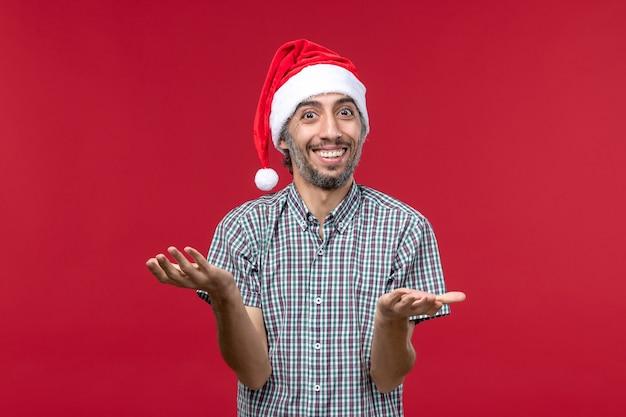 Vue de face jeune avec une expression souriante sur mur rouge vacances nouvel an rouge mâle