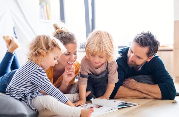 Vue de face d'une jeune famille avec deux petits enfants à l'intérieur dans la chambre en lisant un livre.
