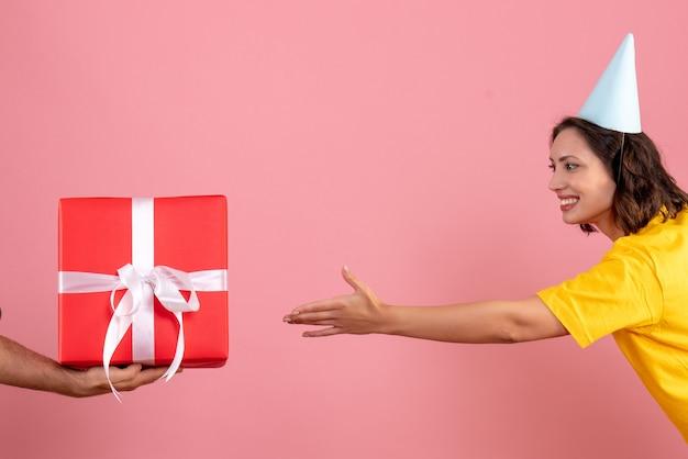 Vue de face jeune femme acceptant présent du mâle sur le rose