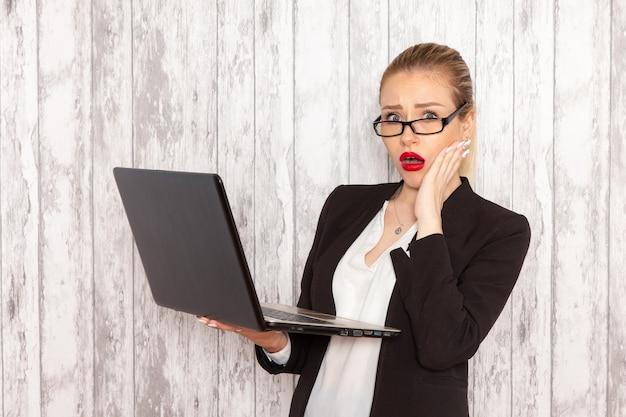 Vue de face jeune femme d'affaires dans des vêtements stricts veste noire à l'aide d'un ordinateur portable sur mur blanc travail travail bureau femme travailleur d'affaires
