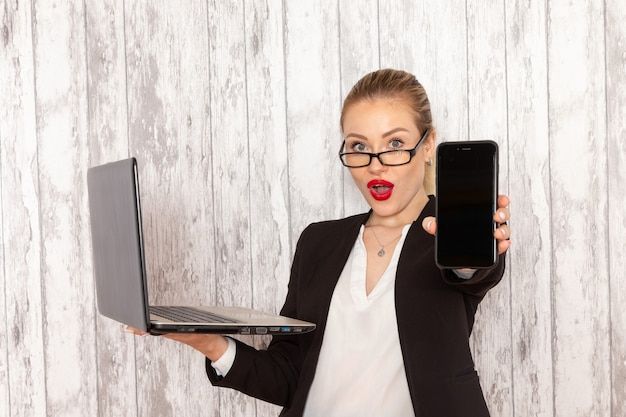 Vue de face jeune femme d'affaires dans des vêtements stricts veste noire à l'aide de son ordinateur portable et tenant le téléphone sur une surface blanche