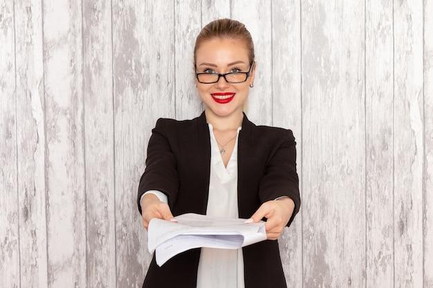 Vue de face jeune femme d'affaires dans des vêtements stricts veste noire donnant un document souriant sur une surface blanche