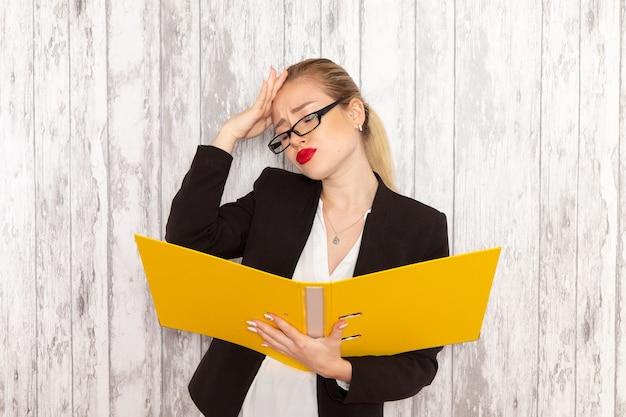 Vue de face jeune femme d'affaires dans des vêtements stricts veste noire tenant des fichiers et des documents sur la surface blanc clair
