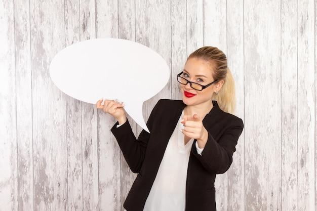 Vue de face jeune femme d'affaires dans des vêtements stricts veste noire tenant grand panneau blanc sur un bureau blanc