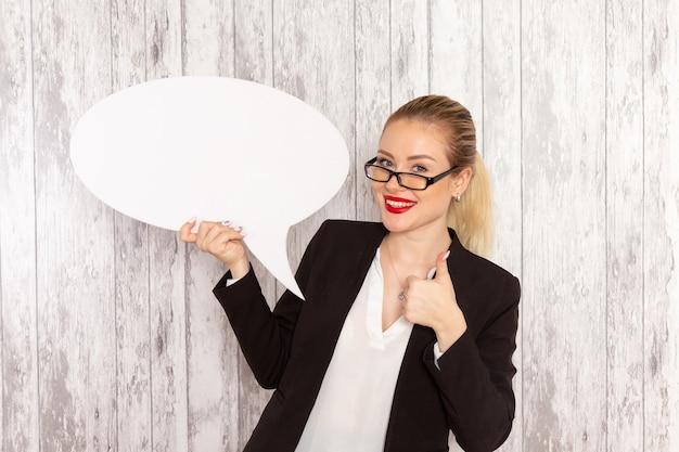 Vue de face jeune femme d'affaires dans des vêtements stricts veste noire tenant grand panneau blanc sur une surface blanche légère