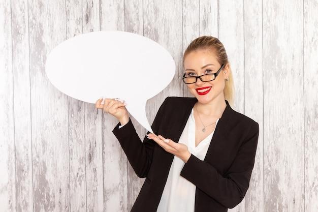 Vue de face jeune femme d'affaires dans des vêtements stricts veste noire tenant grand panneau blanc sur une surface blanche