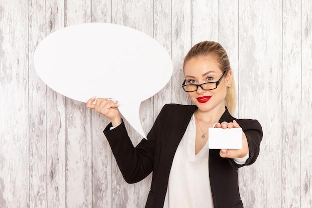 Vue de face jeune femme d'affaires dans des vêtements stricts veste noire tenant une pancarte blanche et une carte sur une surface blanche