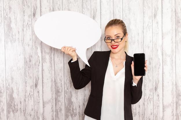 Vue de face jeune femme d'affaires dans des vêtements stricts veste noire tenant son téléphone et panneau blanc sur une surface blanche
