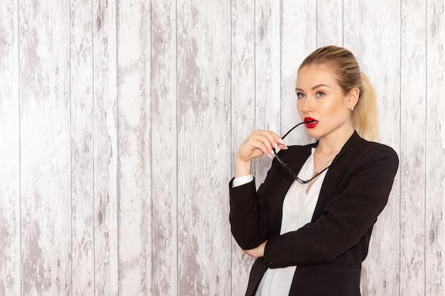 Vue de face jeune femme d'affaires en veste noire de vêtements stricts posant sur une surface blanche