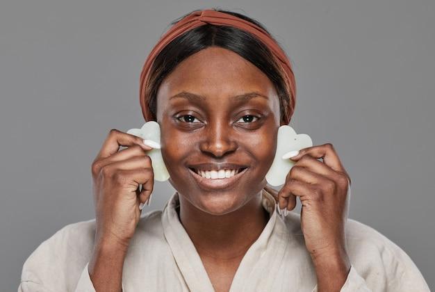 Vue de face sur une jeune femme afro-américaine profitant d'un massage du visage avec des pierres de gua sha et souriant à la caméra