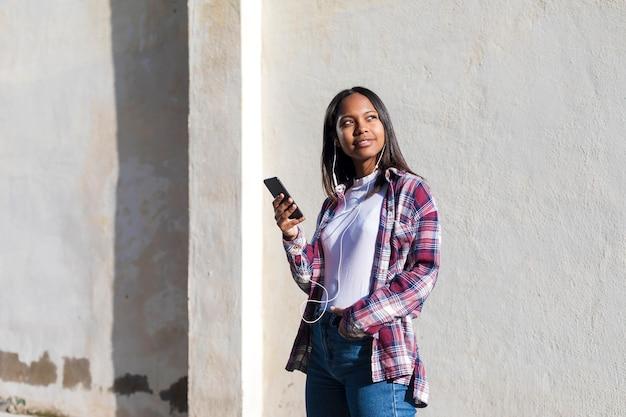 Vue de face d'une jeune femme afro-américaine souriante, debout à l'extérieur tout en souriant et en écoutant de la musique par des écouteurs dans une journée ensoleillée