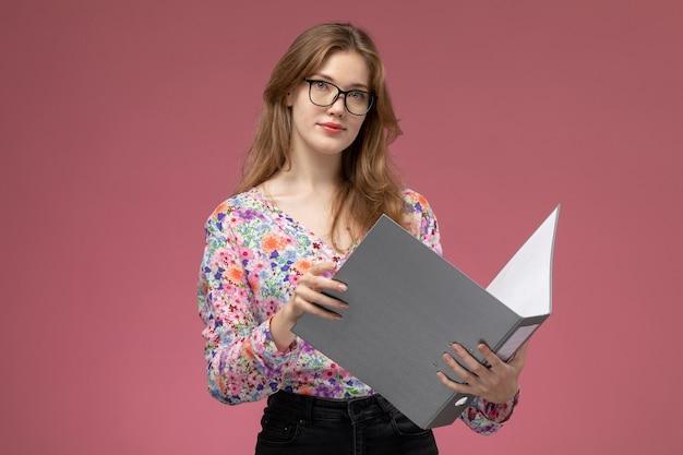 Vue de face jeune femme à l'aide de son document pour découvrir le cas
