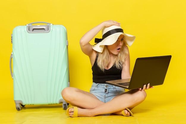 Vue de face jeune femme à l'aide de son ordinateur portable sur mur jaune voyage vacances voyage voyage femme soleil
