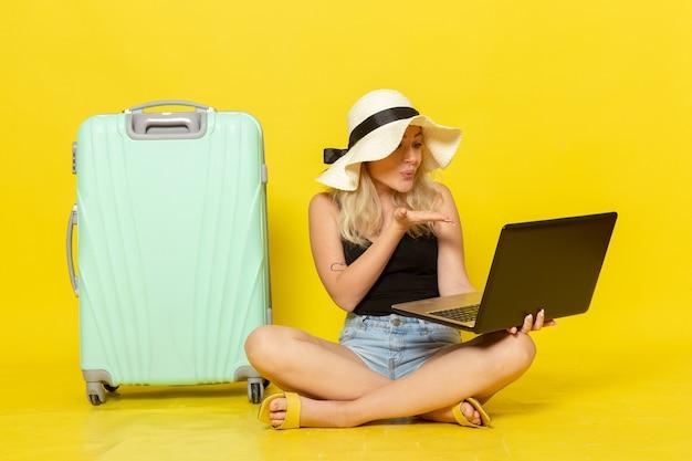 Vue de face jeune femme à l'aide de son ordinateur portable et parler à quelqu'un via vidéo sur mur jaune voyage vacances voyage voyage femme soleil