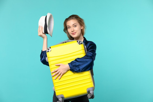 Vue de face jeune femme allant en vacances et tenant le gros sac sur fond bleu mer voyage voyage vacances voyage avion