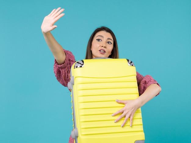 Vue de face jeune femme allant en vacances et tenant le gros sac sur le fond bleu voyage d'été vacances mer voyage femme