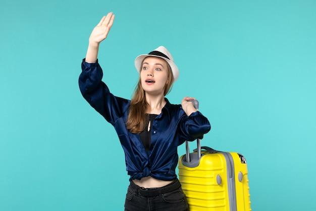 Vue de face jeune femme allant en vacances et tenant le gros sac sur le fond bleu voyage mer vacances voyage voyage