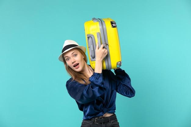 Vue de face jeune femme allant en vacances et tenant un gros sac sur le fond bleu voyage mer voyage vacances voyage
