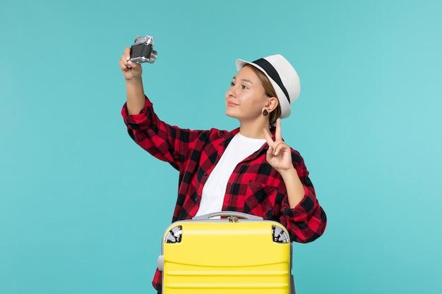 Vue de face jeune femme allant en voyage et tenant la caméra en prenant une photo sur l'espace bleu