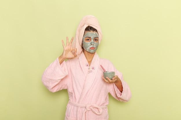 Vue de face jeune femme après la douche en peignoir rose appliquant un masque sur un bureau vert