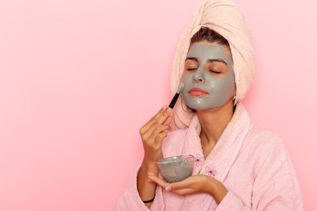Vue de face jeune femme après la douche en peignoir rose appliquant un masque sur une surface rose