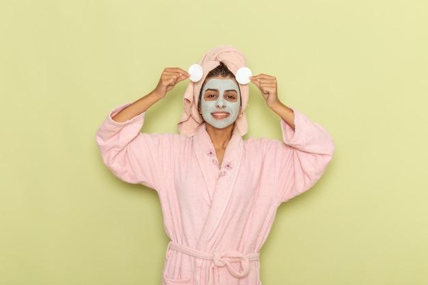 Vue de face jeune femme après la douche en peignoir rose en appliquant peu de coton sur un bureau vert