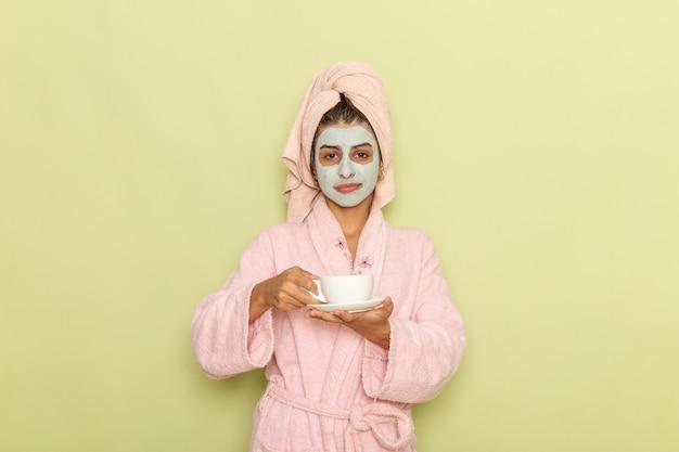 Vue de face jeune femme après la douche en peignoir rose, boire du café sur un bureau vert