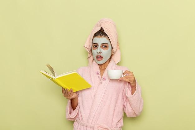 Vue de face jeune femme après la douche en peignoir rose, boire du café et lire un cahier sur un bureau vert