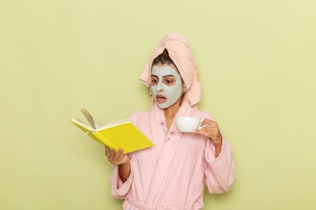 Vue de face jeune femme après la douche en peignoir rose, boire du café et lire un cahier sur une surface verte