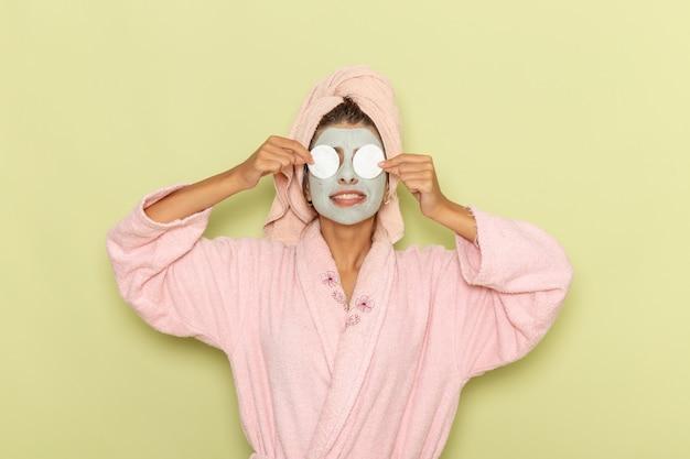 Vue de face jeune femme après la douche en peignoir rose couvrant ses yeux avec du coton sur une surface verte