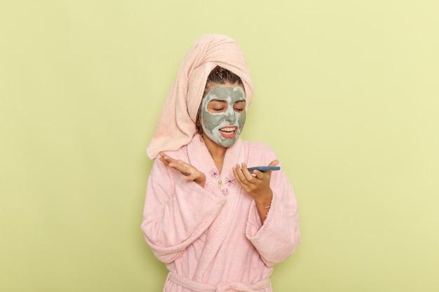 Vue de face jeune femme après la douche en peignoir rose parler au téléphone sur une surface verte