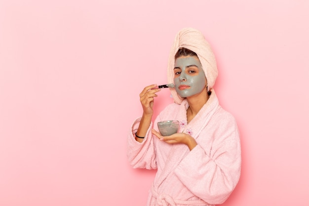 Vue de face jeune femme après la douche en peignoir rose en prenant soin de vous sur une surface rose
