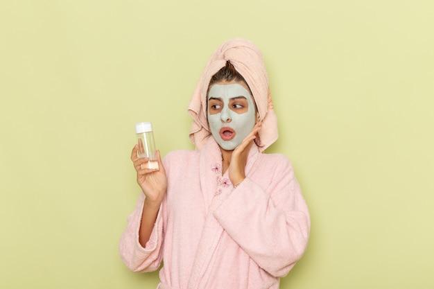 Vue de face jeune femme après la douche en peignoir rose tenant le démaquillant sur la surface verte
