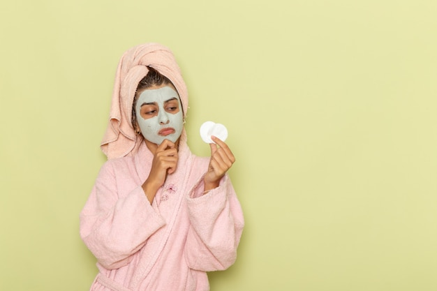 Vue de face jeune femme après la douche en peignoir rose tenant des rondes de coton sur une surface verte