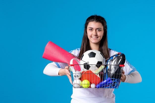 Vue de face jeune femme après le sport shopping sur mur bleu
