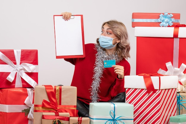 Vue de face jeune femme assise autour de cadeaux avec carte bancaire