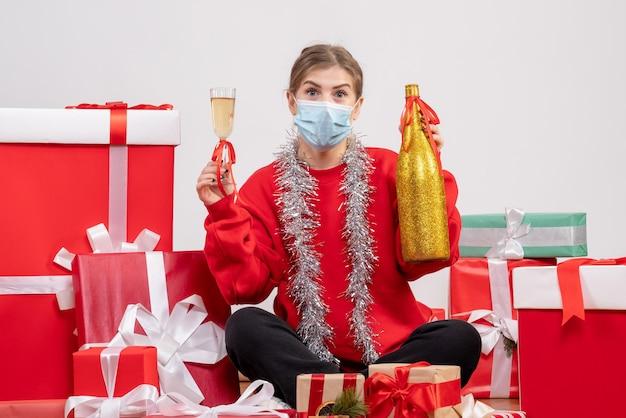 Vue de face jeune femme assise autour de cadeaux célébrant avec champagne