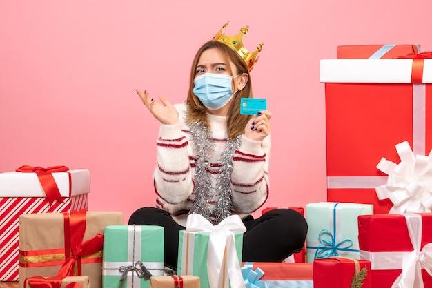 Vue de face jeune femme assise autour de cadeaux de noël avec carte bancaire