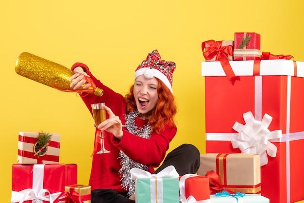 Vue de face de la jeune femme assise autour des cadeaux de noël et célébrer avec du champagne sur le mur jaune