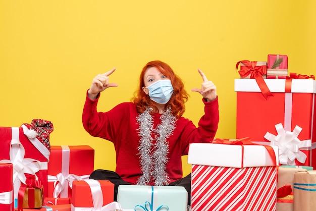 Vue de face de la jeune femme assise autour de cadeaux de noël en masque sur mur jaune